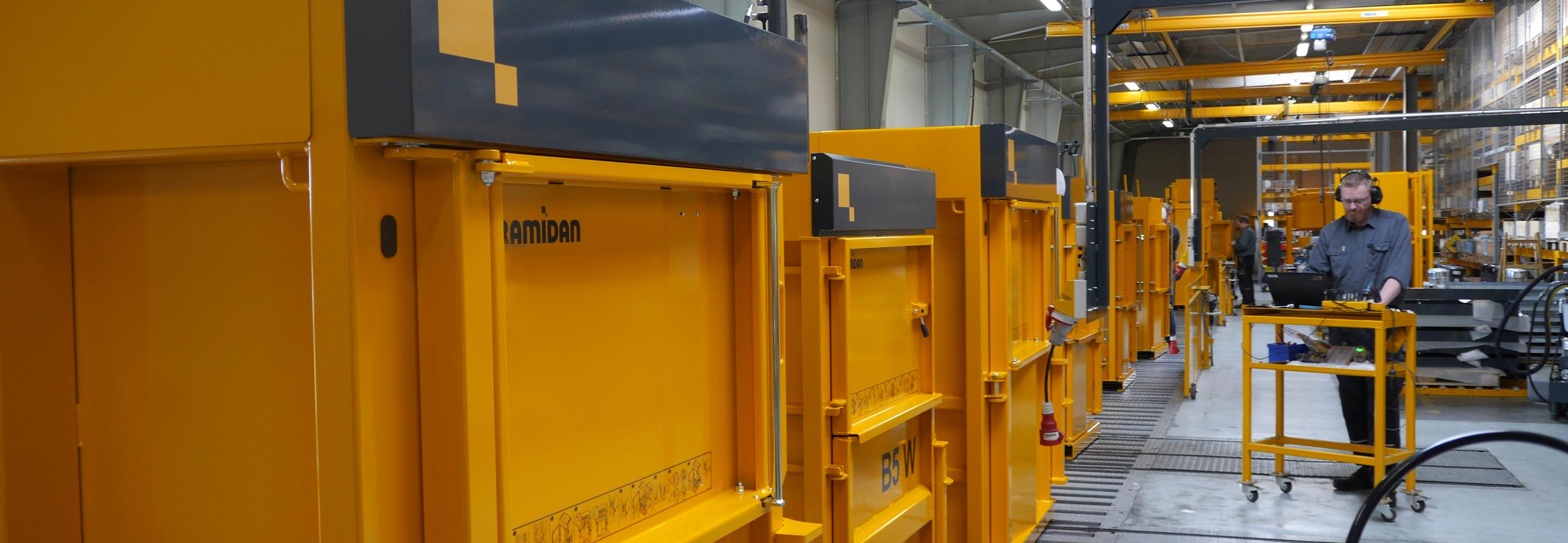 Production line filled with yellow balers and man with earmuffs