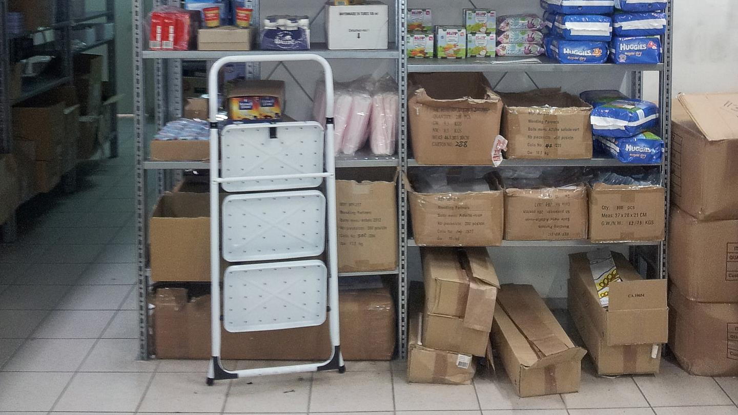 Ladder placed in front of rack with full cardboard boxes