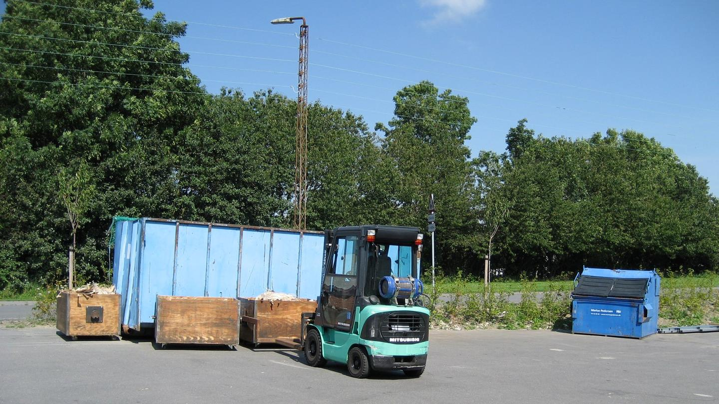 Fork lift truk picks up wooden box with cut cardboard