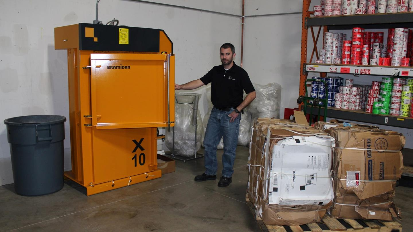 Man next to stock room baler X10 and cardboard bales