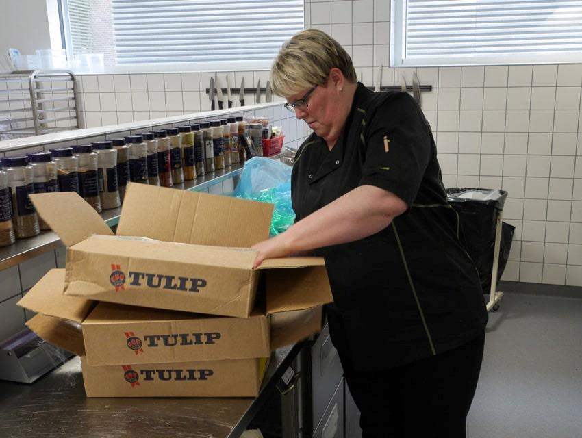 Canteen employee opens cardboard boxes with Tulip meat products