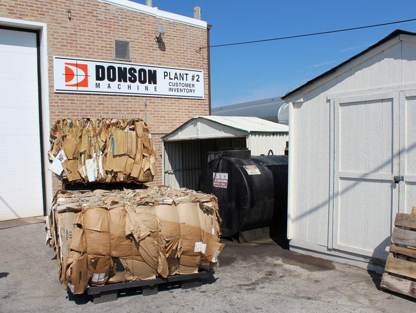Compacted cardboard bales outside company Donson Machine