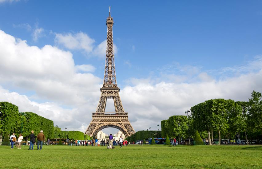 Green lawn with square cut trees and Eiffel Tower in the background