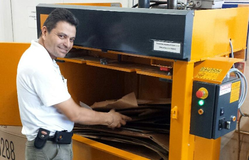 An employee from Herko in Florida fills cardboard in the baler chamber
