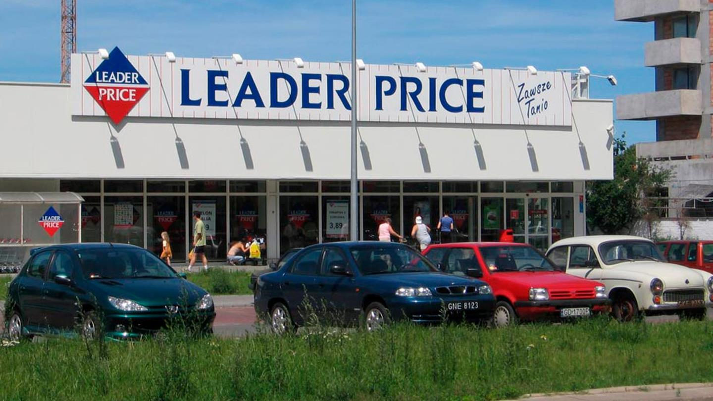 Four private cars parked in front of Leader Price supermarket