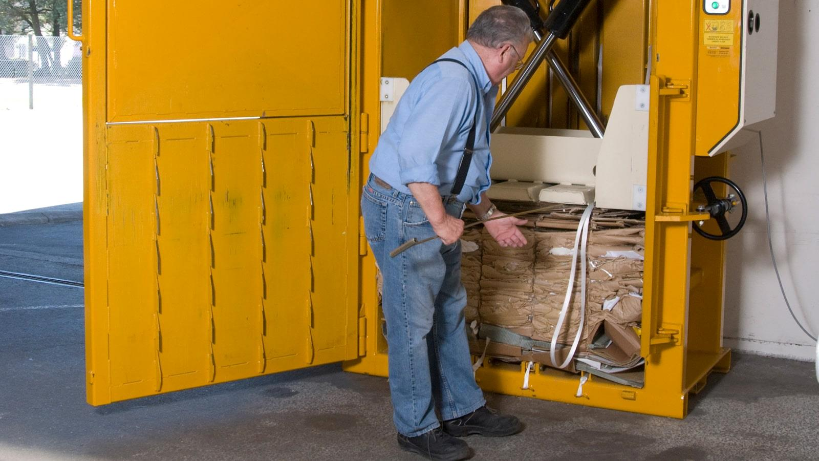 RewAir employee prepares cardboard bale for tying and uses cord hook