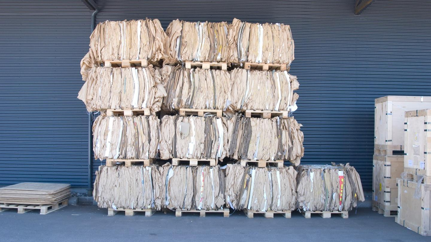 Compacted cardboard bales stacked up against the wall at RewAir