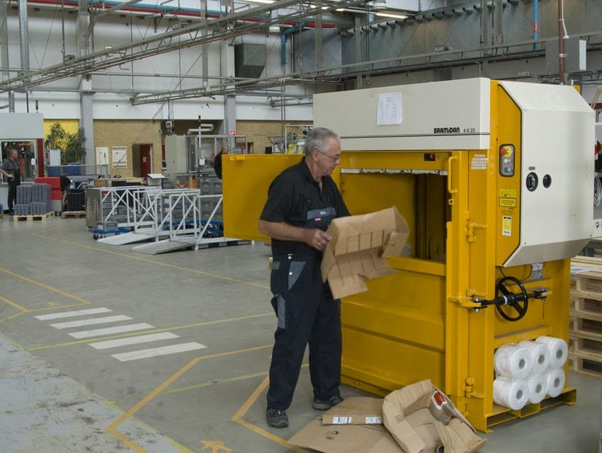 Employee from Sauer-Danfoss fills cardboard boxes into Bramidan baler