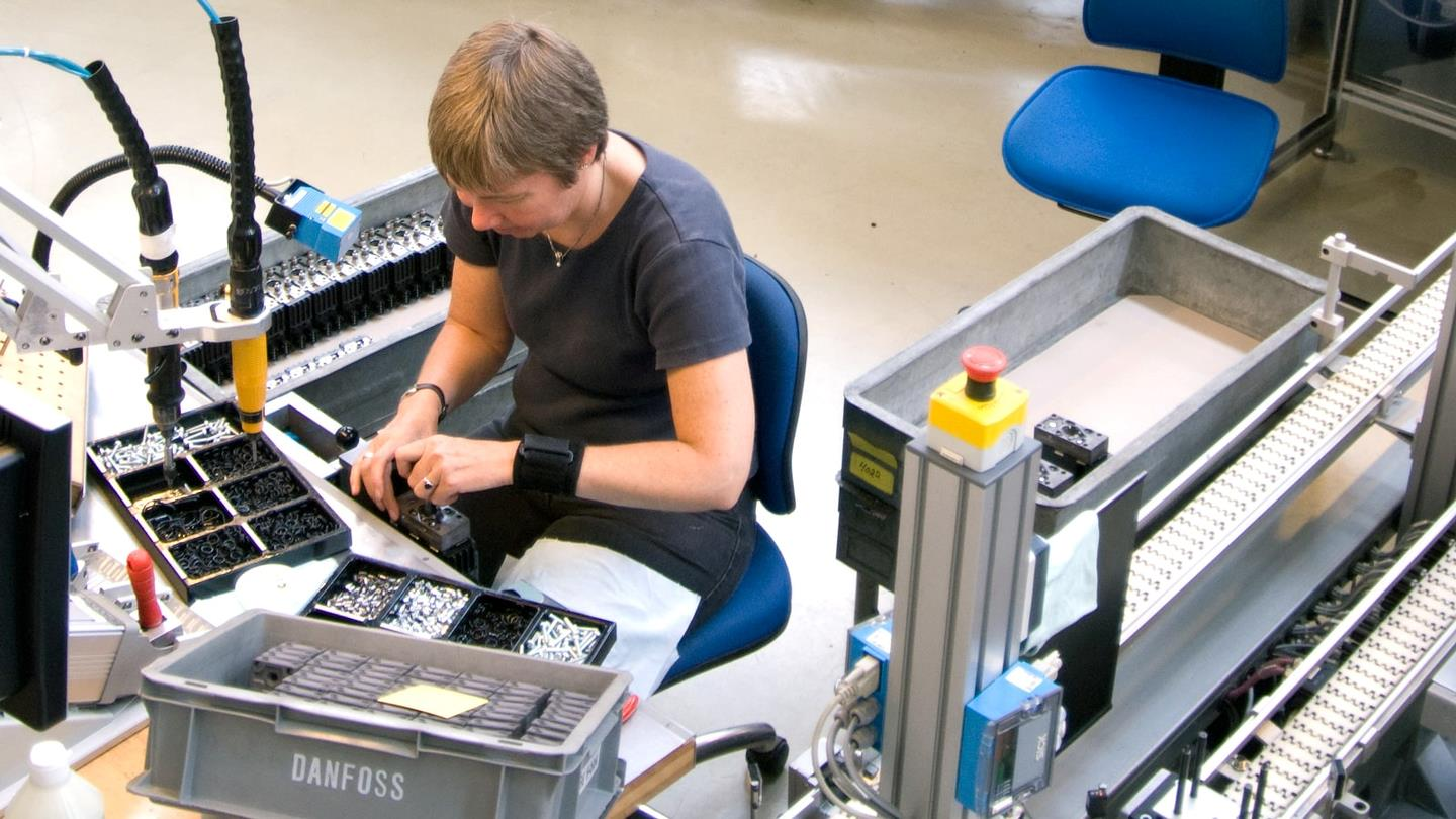 Female worker assembles components at Sauer-Danfoss