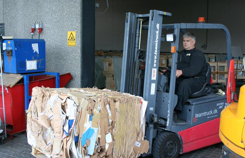 Sunarc employee transports compressed cardboard bale outside with red forklift
