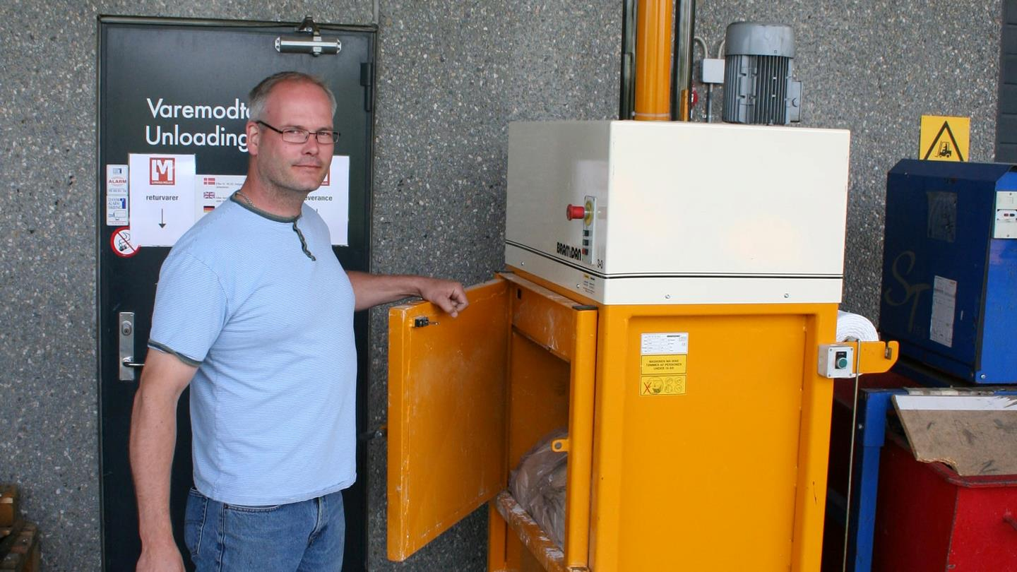 Sunarc employee closes door on yellow Bramidan cardboard baler