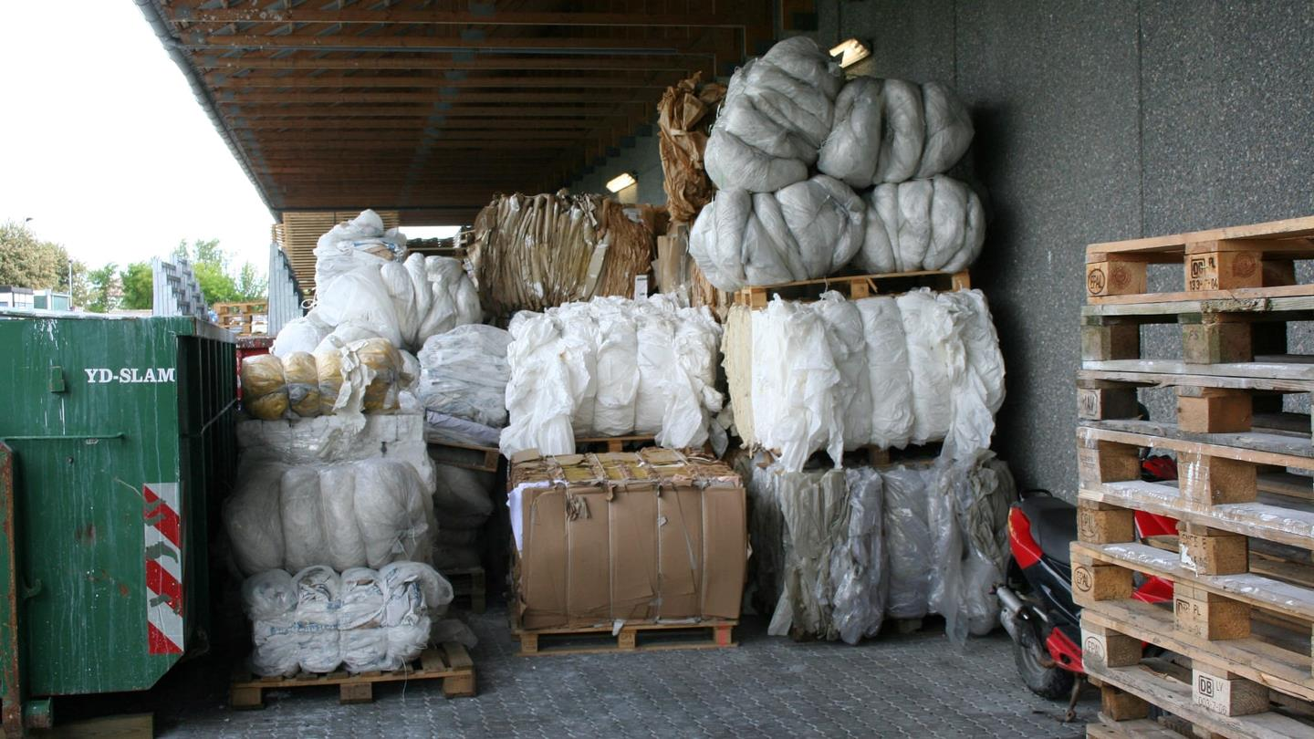 Bales of cardboard and plastic stacked under shelter outside at Sunarc