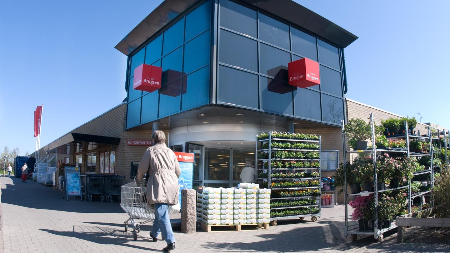 Woman pushes shopping cart towards entrance of supermarket SuperBrugsen