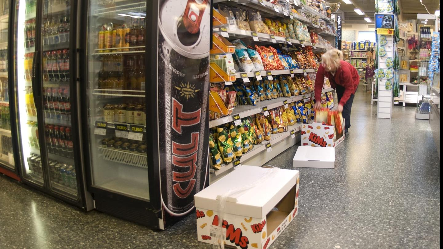 Female employee puts crisps on shelves in SuperBrugsen
