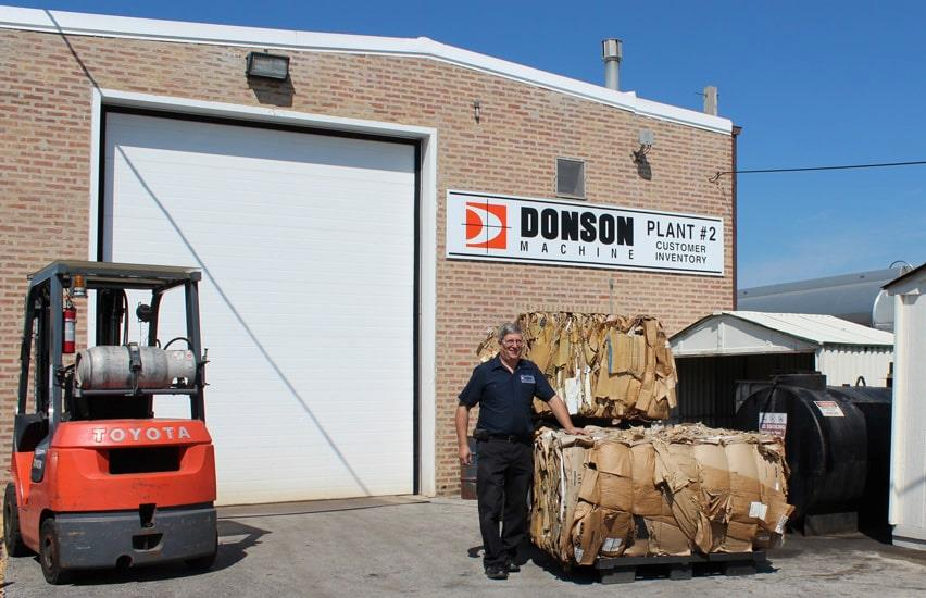 Man next to stacked cardboard bales outside Donson Machine