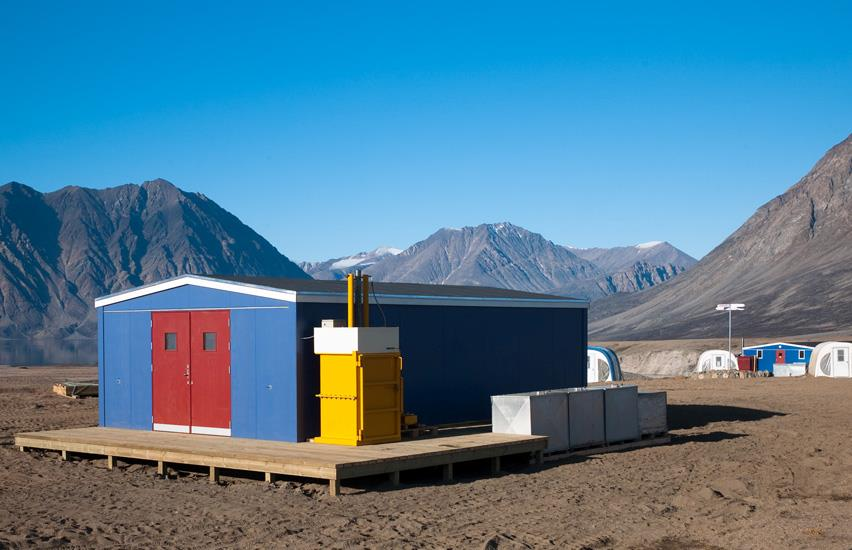 Drum press in front of Zackenberg's work building with mountains behind